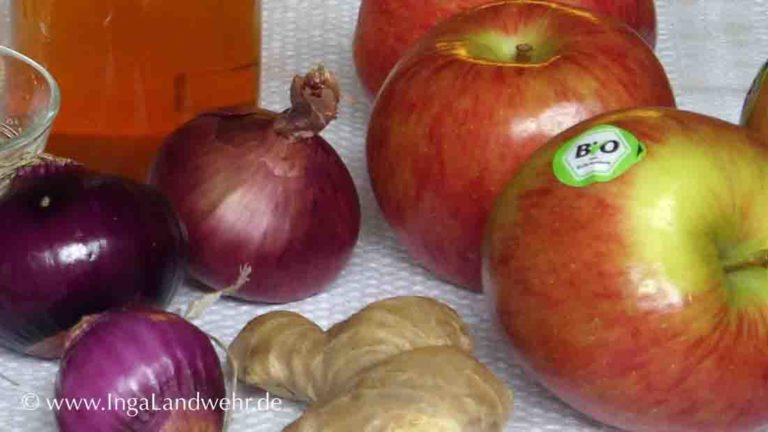 Äpfel, Zucker, Essig, Zwiebeln und Knoblauch liegen auf einem Tisch