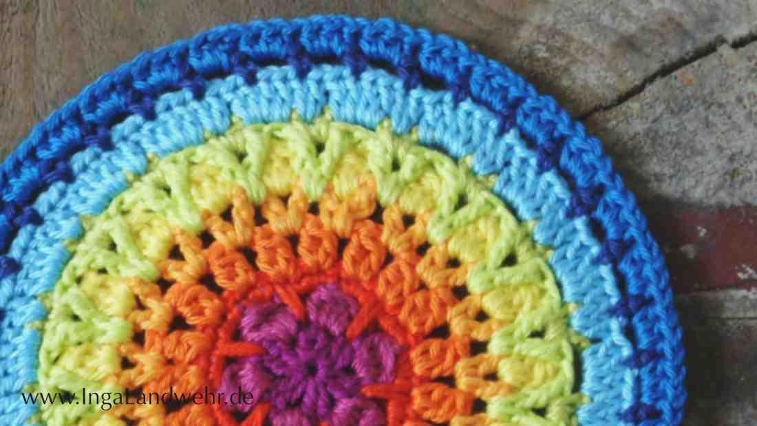 Ein gehäkeltes Mandala in Regenbogenfaben