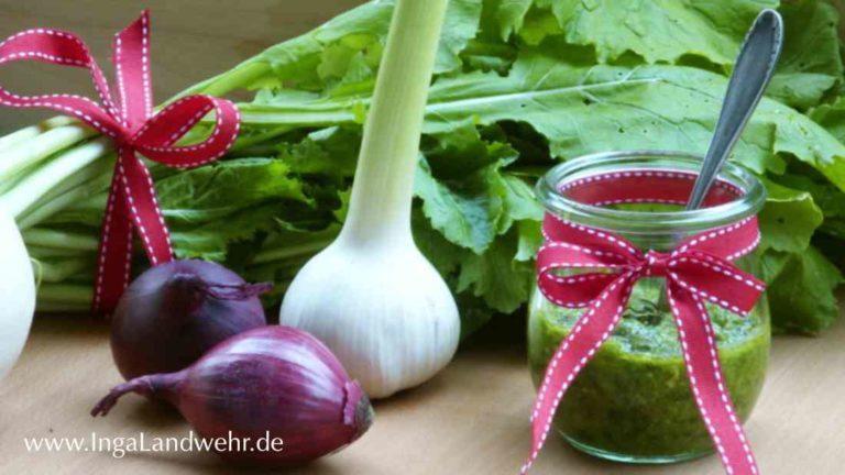 Ein Glas Mairübchenpesto, rote Zwiebeln, Knoblauch sowie ein Bund Mairübchen liegen daneben