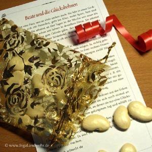 Ein Organzasäckchen und weiße Bohnen liegen auf einem bedruckten Blatt Papier