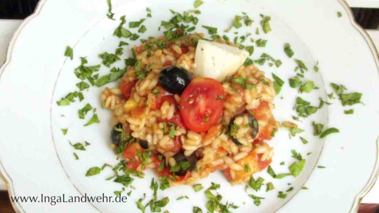 Sommer-Risotto mit Tomaten und schwarzen Oliven auf einem Teller, bestreut mit gehacktem Zimt-Basilikum