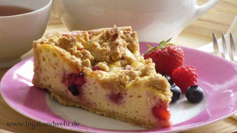 Ein Stück Beeren-Käsekuchen mit Erdbeere und Heidelbeeren auf einem Teller