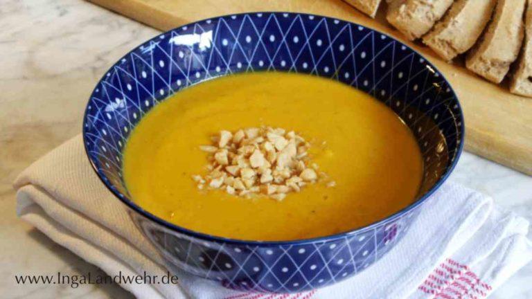 Ein blaue Schale gefüllt mit Kürbis-Suppe. Daruaf sind gehackte Erdnüsse gestreut.