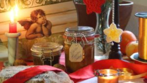 Gläser mit Chutney, Christstollen, Kerzen und gehäkelte Sterne vor einer Keksdose mit Engeln