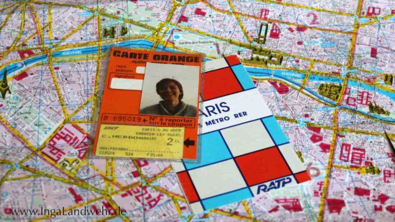 Auf einem Stadtplan von Paris liegt eine Carte Orange und ein Metroplan