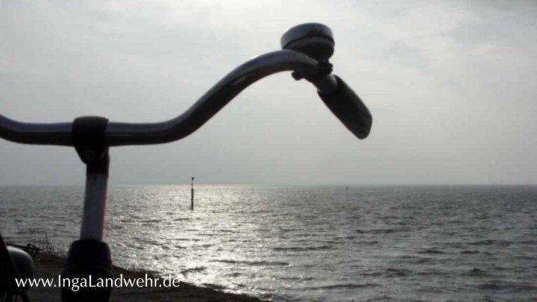 Fahrradlenker im Gegenlicht; Im Hintergrund ist die Nordsee