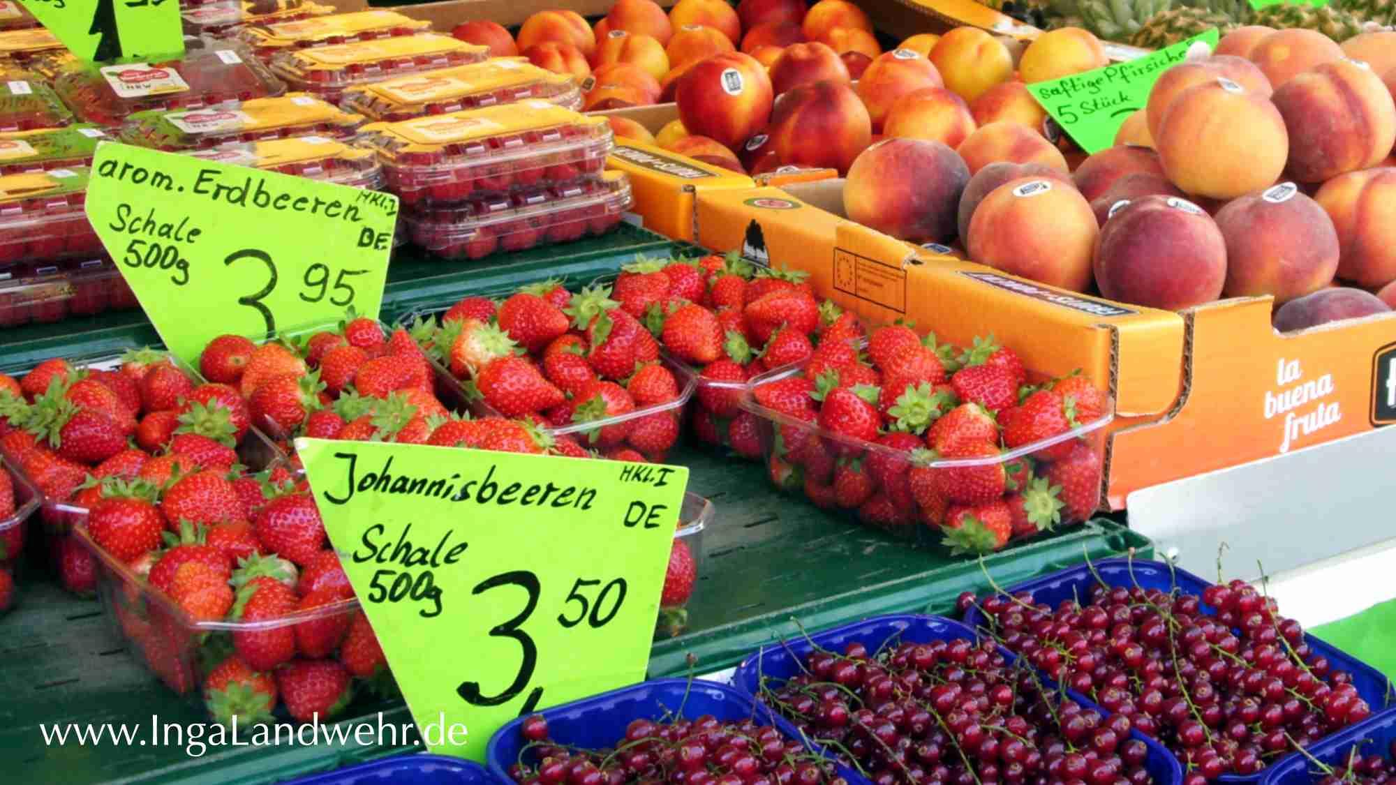Marktstand mit frischen Erdbeeren, Johannisbeeren und Pfirsichen