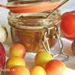 Tomaten-Wildpflaumen-Chutney in einem geöffneten Drahtbügelglas