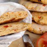 Ciabatta-Fladen mit Tomaten in einer Papiertüte. Daneben liegen Tomatenscheiben.