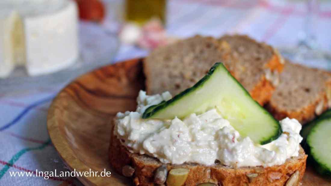 Schafskäsecreme mit Knoblauch auf einem Brot mit Gurke garniert