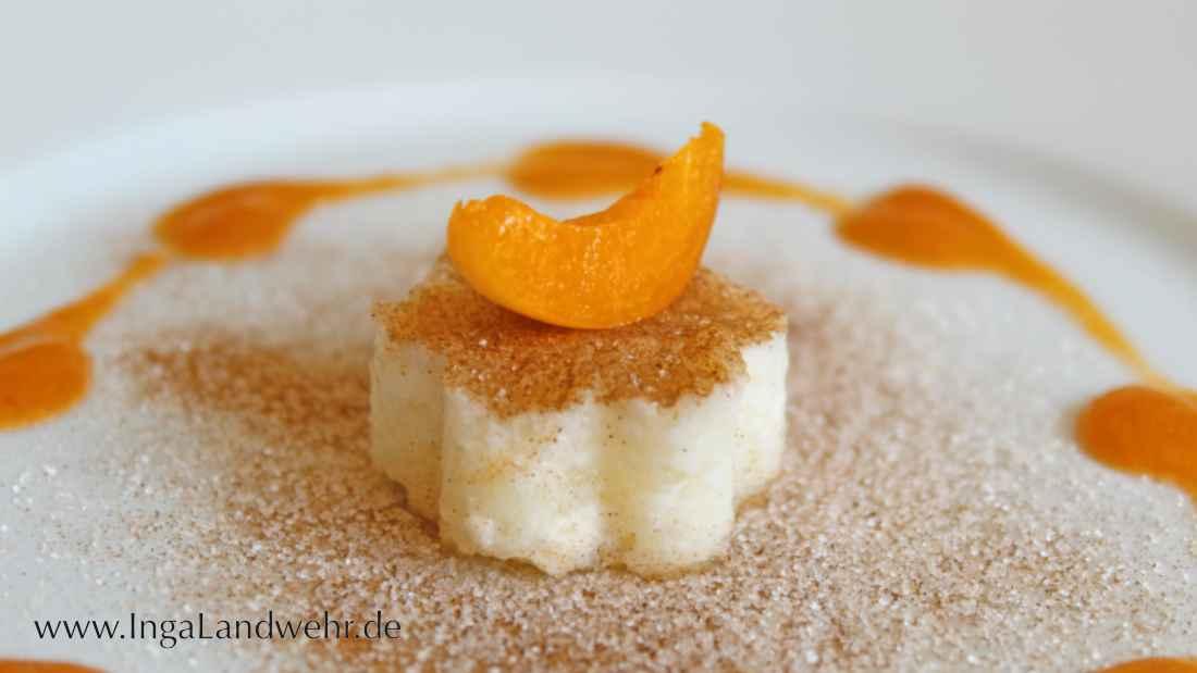 Buttermilchreis in Form einer kleinen Blume mit Zim-Zucker bestreut. DArauf liegt eine Aprikosenspalte.