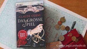 """Neben dem Buch """"Das große Spiel"""" von Claude Cueni liegen Geldscheine und Münzen. Alles liegt auf einer alten Aktie."""
