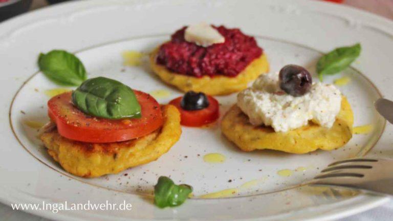 Drei Hüttenkäse-Puffer mit verschiedenen Toppings. Einmal mit Tomate und Basilikum, einmal mit Rote Bete-Aufstrich und einmal mit Schafskäsecreme und schwarzer Olive.