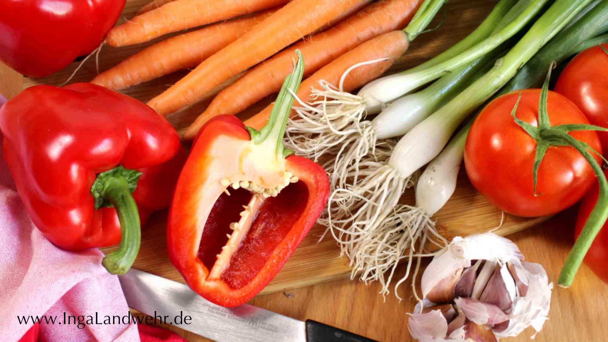 Frische Paprika, Karotten, Frühlingszwiebeln und Knoblauch liegen auf einem Holzbrett