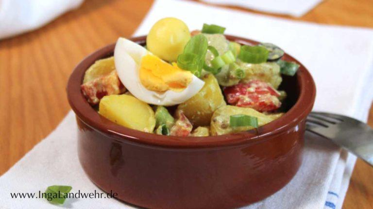 Steingutschale mit Kartoffelsalat, auf dem ein Ei liegt.