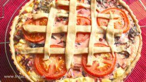 Mangold-Quiche mit Tomatenscheiben und einem Gitter aus Teigstreifen.