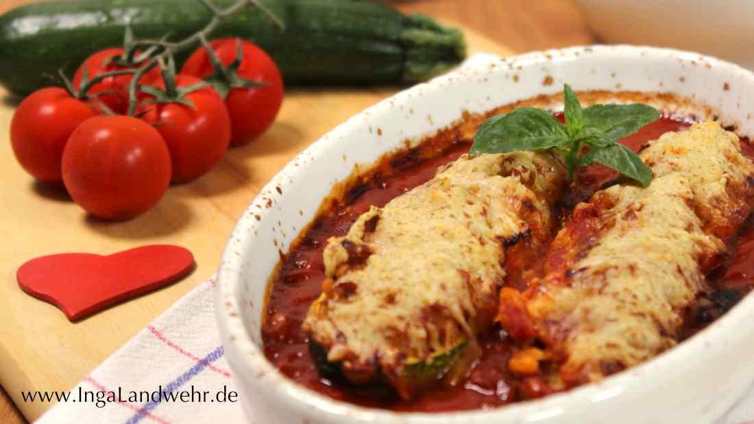Gefüllte Zucchini sind in Auflaufform. Im Hintergrund liegen Tomaten und Zucchini.
