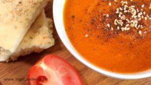 Eine weiße Suppenschale mit Karotten-Tomaten-Suppe. Links daneben liegt eine Tomaten und Lavashbrot.