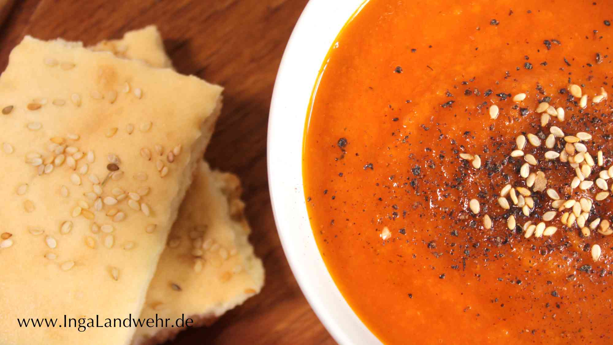 Eine weiße Suppenschale mit Karotten-Tomaten-Suppe. Links daneben liegen ein paar Stücke Lavashbrot mit Sesam.