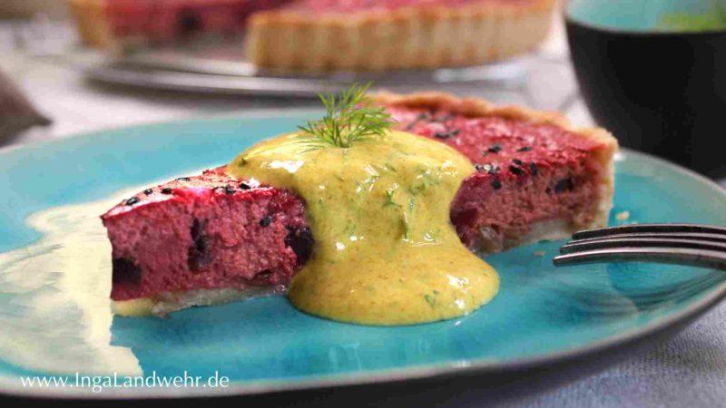 Ein stück Rote-Bete-Quiche mit Feta liegt auf einem türkisfarbenen Teller. Im Hintergrund ist die angeschnittene Quiche zu sehen.