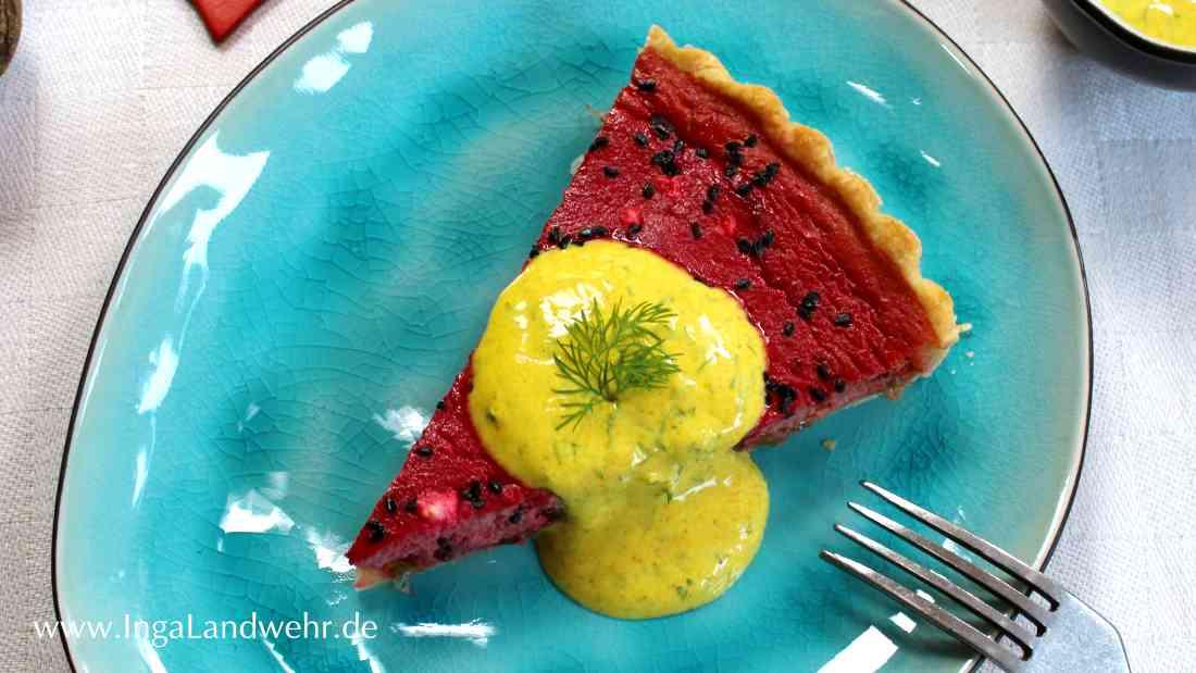 Auf einem ovalen Teller liegt ein Stück Rote-Beete-Quiche. Darauf etwas Joghurtsauce mit Kurkuma.