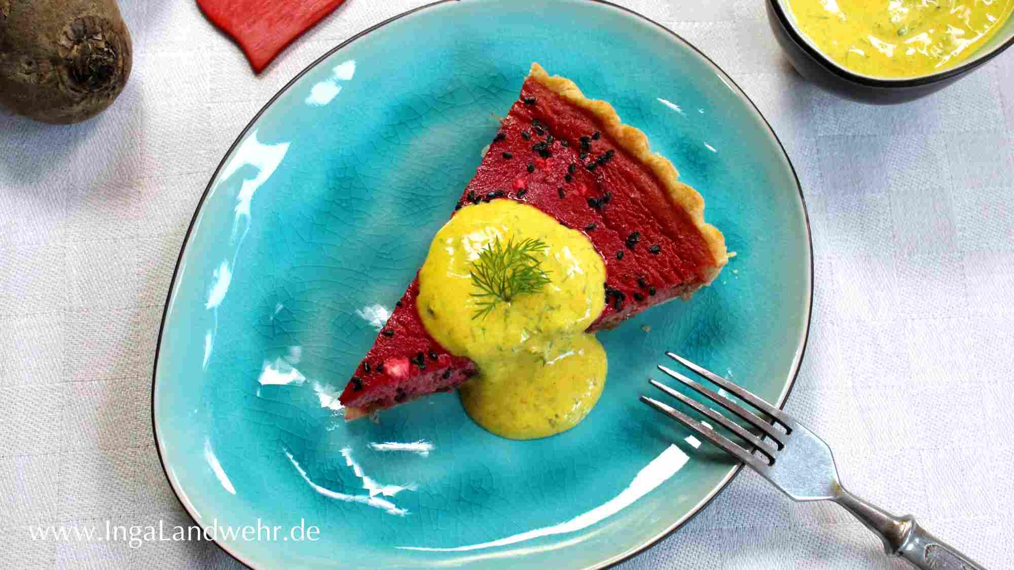 Ein Stück dunkelrote Rote-Bete-Quiche mit sonnengelber Joghurtsauce liegt auf einem türkisfarbenen Teller. Daneben eine Gabel und ein Schälchen mit Joghurtsauce.