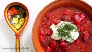 Ein blumen bemalter Löffel liegt links neben einer Tonschüssel mit Borschtsch.