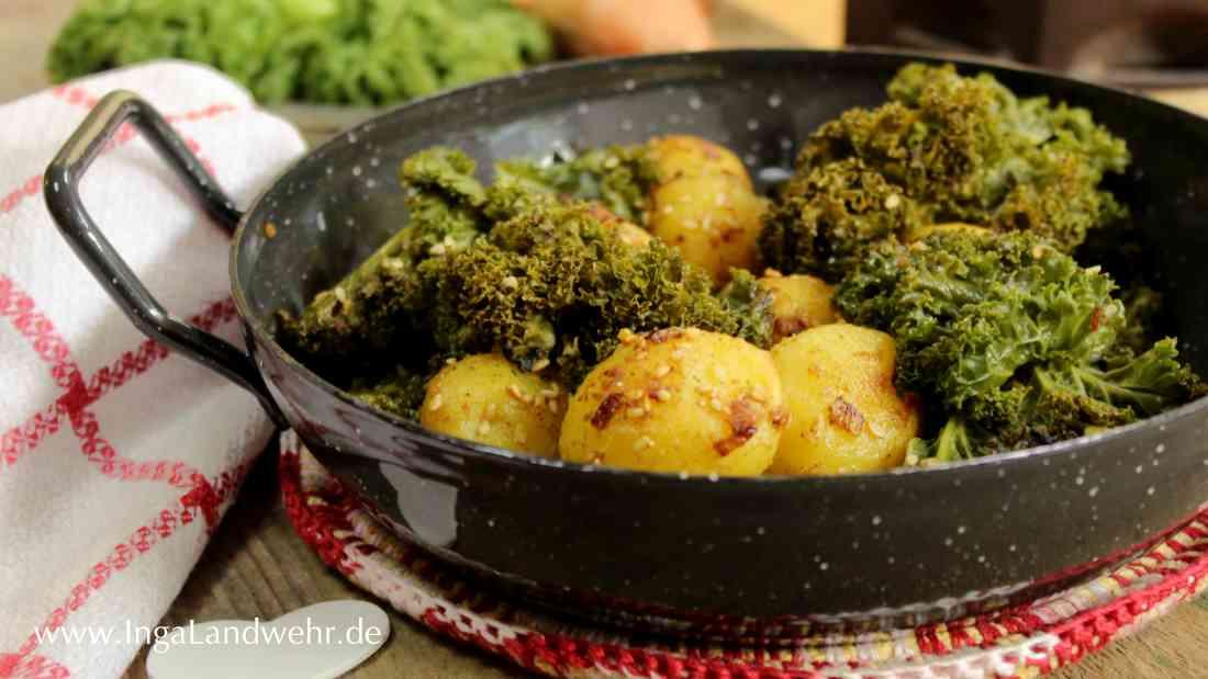 Eine emaillierte Pfanne mit Sesamkartoffeln und Grünkohl steht auf einem rot-weißen Untersetzer.
