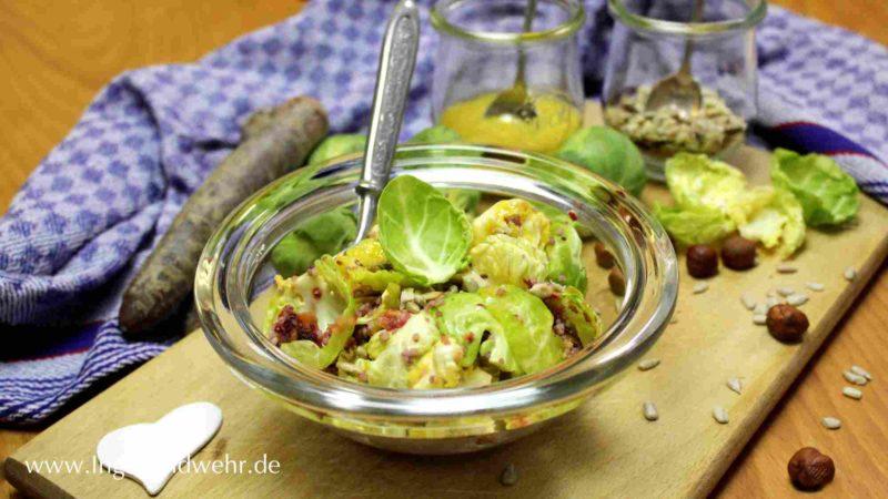 Auf einem Holzbrett steht eine Schüssel mit Rosenkohlsalat. Im Hintergrund steht ein Glas mit Vinaigrette und gerösteten Haselnüssen.