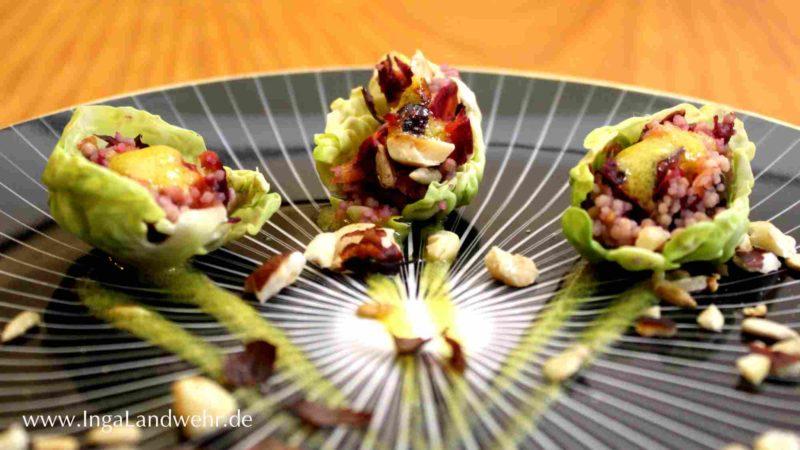 Auf einem schwarzen Teller liegen drei gefüllte Rosenkohlblätter als Fingerfood