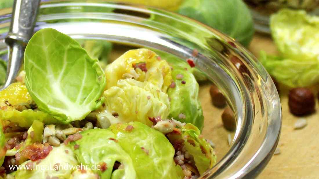 Entblätterte Rosenkohlröschen sind in einer Glasschlüssel mit Bulgur, Haselnüssen und Sonnenblumenkerne angerichtet.