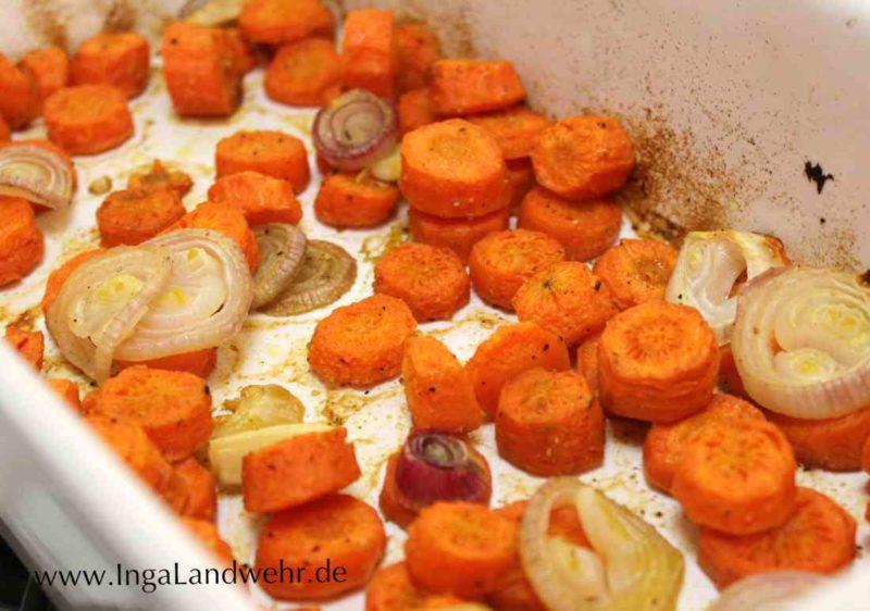 In einer weißen Keramikform liegen im Ofen geroestete Karottenscheiben.