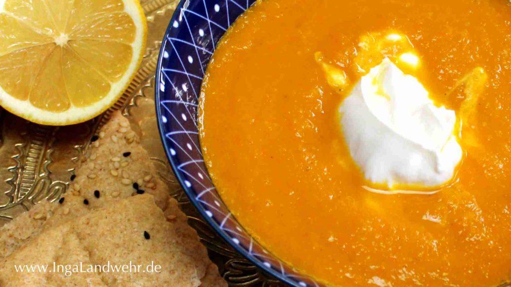 Auf einem Messingtablett stehen eine Zitrone, ein Stück Lavashbrot und eine Schale mit marokkanischer Karottensuppe.