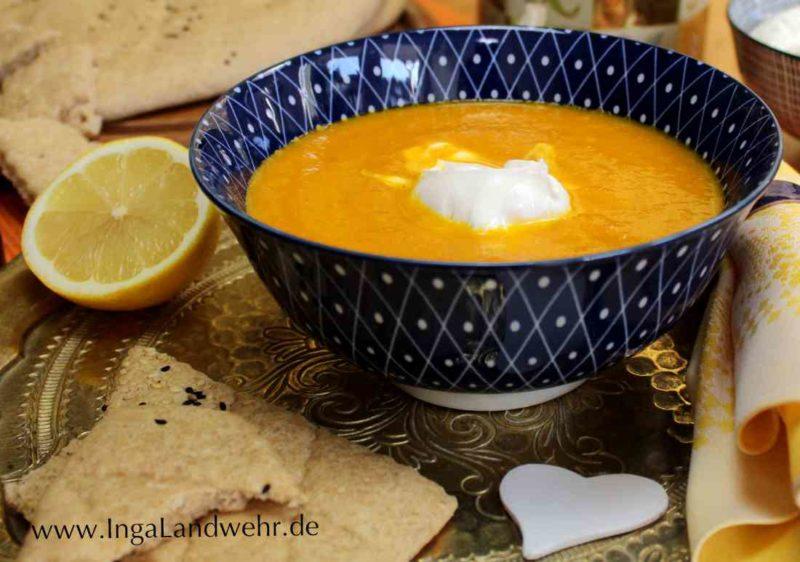 Marokkanische-Karottensuppe, die mit Ras-el-Hanout gewürzt ist, in einer Schüssel, die auf einem Messingtablett steht.