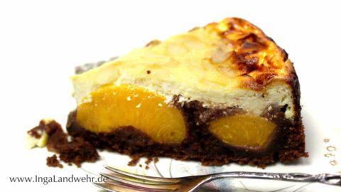 Ein Stück Schokokuchen mit Pfirsich und Käsekuchendecke liegt auf einem Teller. Davor liegt eine Kuchengabel.