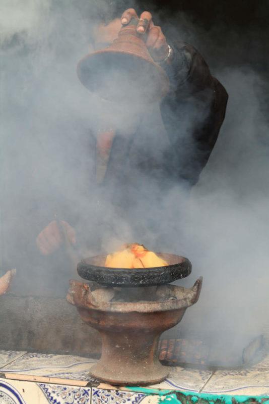 Eine Tajine mit Gemüse gart auf einem Holzkohlenfeuer.